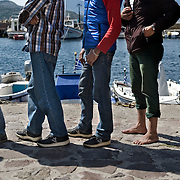 Refugees at the port of Molyvos, Lesbos island, forming a queue at a soup kitchen organised by locals.  The people of Lesbos island, many of whom come from families that were refugees themselves, provide meals and cloths for the refugees everyday. Everyday hundreds of refugees, mainly from Syria and Afghanistan, are crossing in small overcrowded inflatable boats the 6 mile channel from the Turkish coast to the island of Lesbos in Greece.