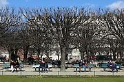 Couples enjoy the winter sun outside Notre Dame, Paris