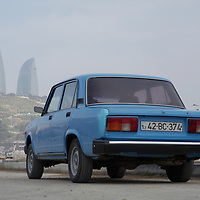 A classic Lada car sits in a parking lot looking out towards the new Flame Towers in Baku, Azerbaijan.