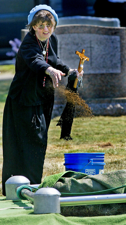 08/14/06 Boston, MA-- Terina Davulis throws a handful of earth on the casket of one of her sons at New Calvary Cemetery Monday.  Her son William, 26, died in a motorcycle accident hours before her son Dominic, 17, died of a brain tumor.  (081406funeralar01, saved in tues, Staff Photo by Angela Rowlings)