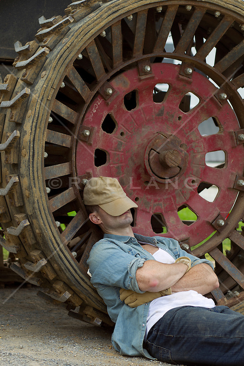 farmer taking a break from work and resting by a large tractor tire