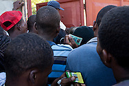 People hold identification cards as they wait to obtain voter registration cards on Tuesday, November 23, 2010 in Port-au-Prince, Haiti.
