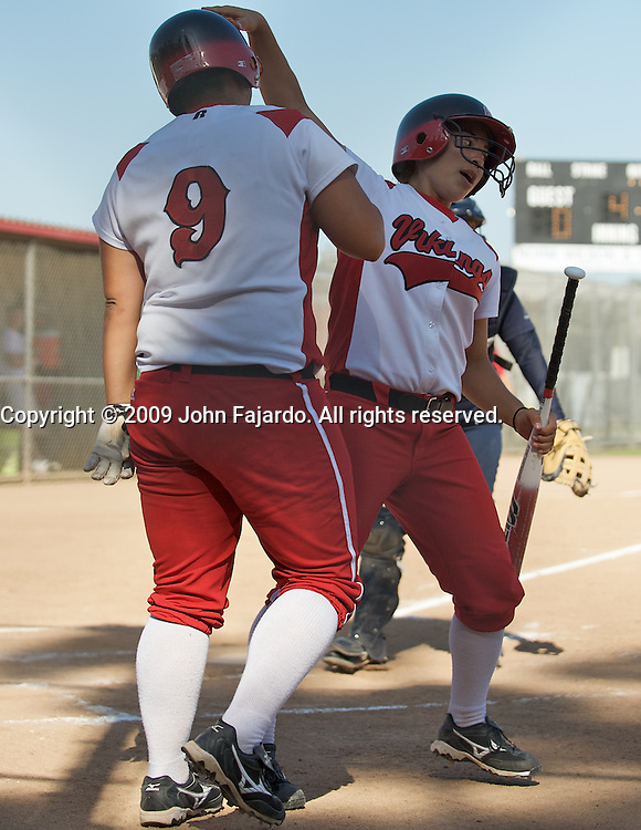Monique Ogata gets a pat on the head from Caitlin Lopez after Ogata scored in the game against South Coast Conference rival El Camino College at the LBCC Softball Field on Tuesday April 7, 2009.  The Vikings win 10-0 when El Camino failed to score in the fifth inning.