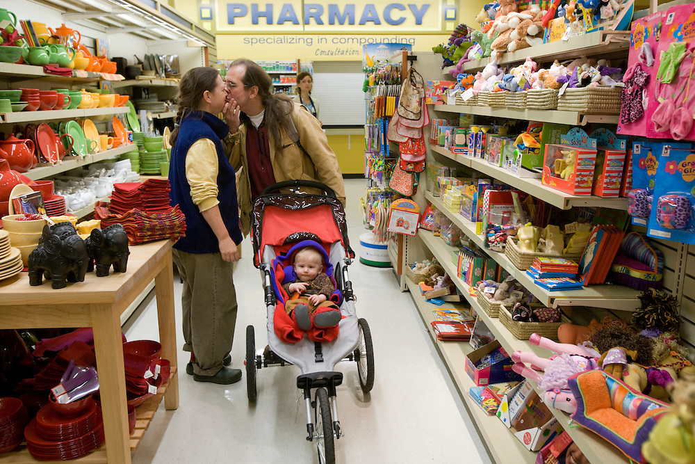 USA, Oregon, Portland, Middle-aged husband and wife with young son in stroller walking in grocery store aisle