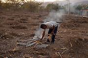 A member of the Community Police prepares a bonfire in the middle of a harvest field, before bringing prisoners to their reeducation program. / Un policía comunitario prepara una fogata en medio de un campo de cosecha antes de llevar a algunos detenidos para el programa de reeducación.  (Photo: Prometeo Lucero)