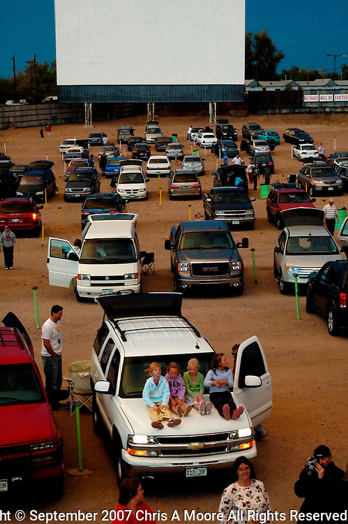 Kids line up on an SUV watching the action at the snack bar before the last show at Cinderella Twin Drive-in.