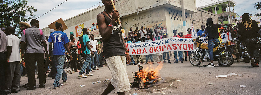 A fire burns in an intersection at the start of an anti-government protest on Tuesday, December 16, 2014 in Port-au-Prince, Haiti. President Michel Martelly was elected in 2010 with great hope for reforms, but in the wake of slow recovery and parliamentary elections that are three years overdue, his popularity has suffered tremendously, forcing Prime Minister Laurent Lamothe to resign.