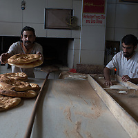 An ekmekci, or baker, moves pide from oven to cooling board at a firin in Kars, in Turkey's northeast.