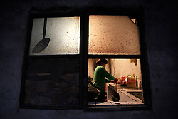 Thick grime and dust as a result o pollution from a nearby chemical plant is seen on the window panes of a house as a villager of Xiangnan Village cooks in her home in Zekou Town, Qianjiang City of Hubei Province, China 15 January 2013. While the heavy smog in Beijing and much of northern China in recent days have caused alarm among residents and renewed scrutiny on the pollution woes of the country, villagers in a small town of Hubei Province have been grappling with severe air, water and noise pollution on a daily basis over the past two years. China's Xinhua news reported 04 January 2013 that more than 60 cancer deaths in various villages of Zekou Town has been caused by the heavy pollution from the chemical industry park nearby. About 20 or more chemical plants built around the villages of Dongtan, Xiangnan, Zhoutan, Sunguai, Qingnian and others over the past two years has created huge increases in noise, air and water pollution. Many villagers complained of intensifying respiratory, heart, skin and circulatory illnesses caused by the pollution and a large spike in cancer diagnoses and deaths since the factories were built. .