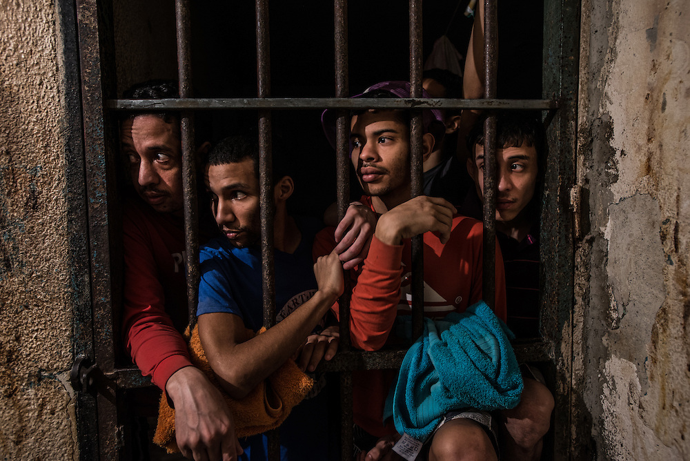 CARRIZAL, VENEZUELA - NOVEMBER 15, 2016:  Men arrested for stealing talk with visiting journalists at the jail in El Carrizal.  The majority of the men had held regular jobs their entire lives, but turned to crime once the economic crisis sharply devalued their salaries, and they could not afford to support their families anymore.  Conditions in Venezuelan jails are inhumane. Those detained have to rely on family members to bring them food and water and personal items, but most come from working class families that are struggling to eat because of the economic crisis and skyrocketing food prices in Venezulea - that most cannot spare food to bring to their family members, or pay the bus fare to bring it to them.  The men said they are always hungry, and usually only eat one cup or rice or one piece of bread a day each. They showed signs of being undernourished, and claimed to have lost dozens of pounds each since being detained.  The jails are overcrowded and the justice system is over capacity for processing cases, causing men in local jails to wait several months, and some several years, before having their case processed.  PHOTO: Meridith Kohut for The New York Times