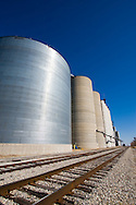 A large grain storage bin sits in a small rural town along the railroad tracks.