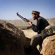 A Northern Alliance fighter crouches in a trench on the  front line near Korogh, Afghanistan on October 12, 2001.