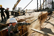 Specialist Steve Clark of the 115th Group of the Utah National Guard shovels sand while building a new fence along the US-Mexico border near San Luis, AZ on Wednesday, June 7, 2006.<br />