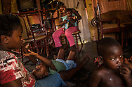 EL SEIBO, DOMINICAN REPUBLIC - OCTOBER 12, 2013: Lucita Edme, 27, (left) and Jaquelin Dosine, 29, (center) take care of their children at their home in a batey  on a sugarcane plantation in El Seibo. They were born in the Dominican Republic, and their children were also, however since their parents were born in Haiti, Edme and Dosine and all of their children are affected by judgment TC/0168, handed down by the Constitutional Court of the Dominican Republic.  The ruling essentially revokes Dominican citizenship from tens of thousands of people born in the Dominican Republic, which means they cannot have access to government services, id's necessary to travel and work, and the children cannot attend public school. The Inter-American Commission on Human Rights has expressed that the ruling would leave affected people stateless, which is a violation of the American Convention on Human Rights.