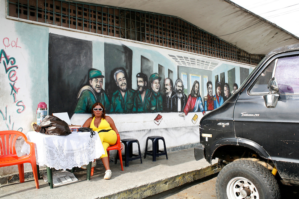 "A women in the 23 de Enero barrio in Caracas rents cell-phones underneath a mural of Venezuela's own version of ""the last supper""."