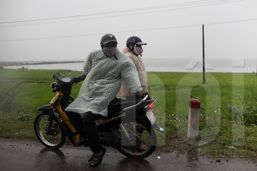 A couple waiting friends on the highway 1 to Danang, Vietnam, Asia. They wear rain coat.