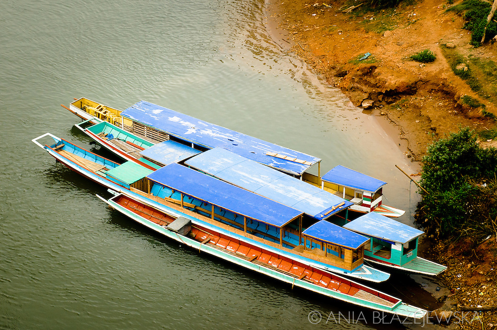 Laos, Nong Khiaw. Colorful boats used for transport on Nam Ou.