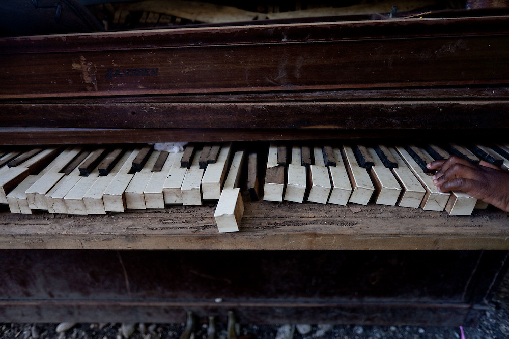 A child plays on a broken piano. In much of rural Haiti children lack access to education and health care.