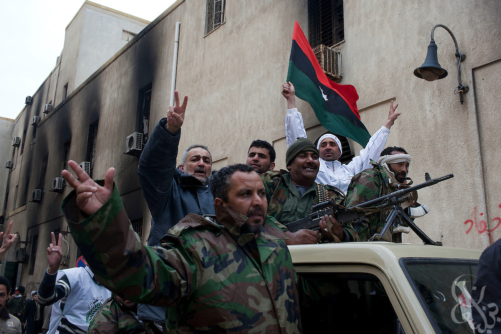 Libyan soldiers that have joined the revolution celebrate atop their vehicle as they transport reclaimed weapons that have been turned in by civilians February 25, 2011 near the central square of Benghazi, Libya. Several former soldiers also said that some 250 defected soldiers from a barracks near Benghazi had left for Tripoli to join the fight nearer to the capital, Tripoli..Slug: Libya.Credit: Scott Nelson for the New York Times