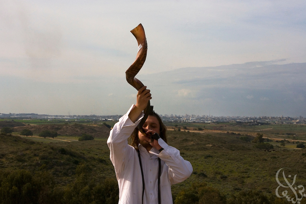 An Israeli member of the Jewish Breslav Hassidim sect plays a Shofar, a horn made out of a rams horn as he and other sect members and townspeople of Sderot watch the ongoing Israeli Defense Forces attack on nearby Gaza (seen behind) January 08, 2009 from a hilltop in Sderot, Israel.