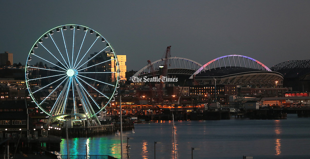 The Seattle Great Wheel glows in the early evening, along with CenturyLink Field.<br />