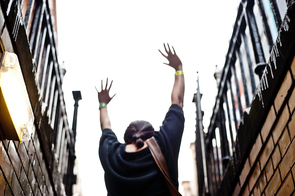 Manchester, UK - 4  August 2012: a woman  raise her arms to the sky exiting a pub in a basement.