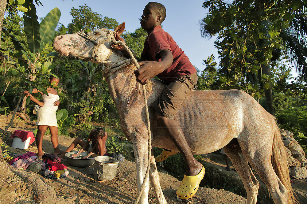 A youngster tries to control his horse at the natural spring as others wash their clothes high up the mountain above Carrefour, Haiti.  The spring is the only natural source on the mountain and people walk for hours up the mountain to collect water, bathe and wash their clothes.  Once done they will fill buckets with water and carry it back to their homes.