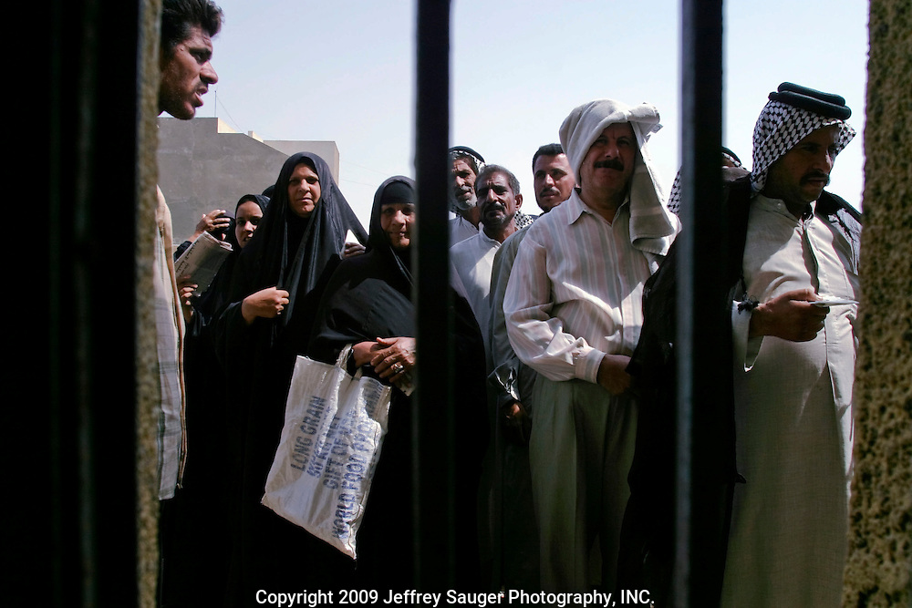 Iraqis wait in line for a $40/month social security payment as other wait for theirs in Nasiriyah, Iraq, Tuesday, August 12, 2003. The director of the program said he receives $2 million per month from the Coalition Provencial Authority and because of the number of people they provide for can only give out $40/month payments.