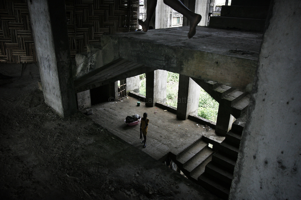 "Photo taken 19 September 2005 of an interior view of the former uncompleted Ministry of National Defense building in Congo Town on the outskirts of Monrovia. The ""Pentagon"", named this way by its occupants, shelters 394 families totalling approximately 3,000 people who were booted out in May 2005 of the Barclay Training Center, which had been their home for the last two decades. Former soldiers, who fought for former Liberian presidents Samuel Doe and Charles Taylor, live in this building with no water or electricity, overcoming past differences. The construction of the building started in 1984 under Doe's leadership, and the war interrupted the its completion and later served as a base for Taylor's men."