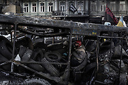 Sitting on pile of tires in a charred police bus, an anti government protester stands guard on Hrushevskoho street barricades near Maidan Square during standoff with riot police while a truce was agreed, in Kiev, 27 January 2014.