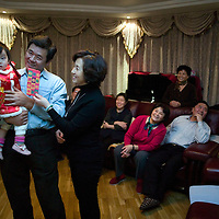 BEIJING, 25. JANUARY, 2009 :   Mr's Li's grandchild receives a traditional &quot; hong bao&quot; ( red envelope filled with money) during new year festivities.<br /> Mr. Li, a paper factory owner, is facing one of his most difficult times .&quot; Last November the market suddenly went down ,&quot; Li says.   <br /> He had bought paper, a lot of paper, and paid 7000 Yuan/ t .<br />  Li's company buys paper from paper mills and lives from the sales to publishing houses and other companies.  Since the market's collapse , he manages to sell the paper only for 6000 Yuan/t.<br /> His clients' export business to the USA had shrunk in Southern China. Mobile phone manufacturers don't need paper for the instruction guides to their mobile phones anymore as their US clients buys less China- made mobile phones.<br />  Toy manufacturers don't need paper anymore  because Americans import less toys from China. &quot; The crisis has driven many of my clients into bancruptsy&quot;, says Li.<br />  <br /> China's Communist Party  which will celebrate its 60th anniversary in October, currently faces its biggest challenge since the beginning of the economic reforms 30 years ago  : &quot; The phase of  rapid economic growth is over. For the first time the government is threatened with a  mistrust of a wide section of the population&quot;, warns the Communist party's Shang Dewen in Beijing.   <br /> Not only the China's poorest worry about the furture, but as well China's middle class is concerned about the crisis.     1,5 Millionen university graduates didn't find a job until the end of 2008  and this summer there'll be an additional  6,1 Million new graduates. More than 12 percent of university graduates face unemployment in 2009.