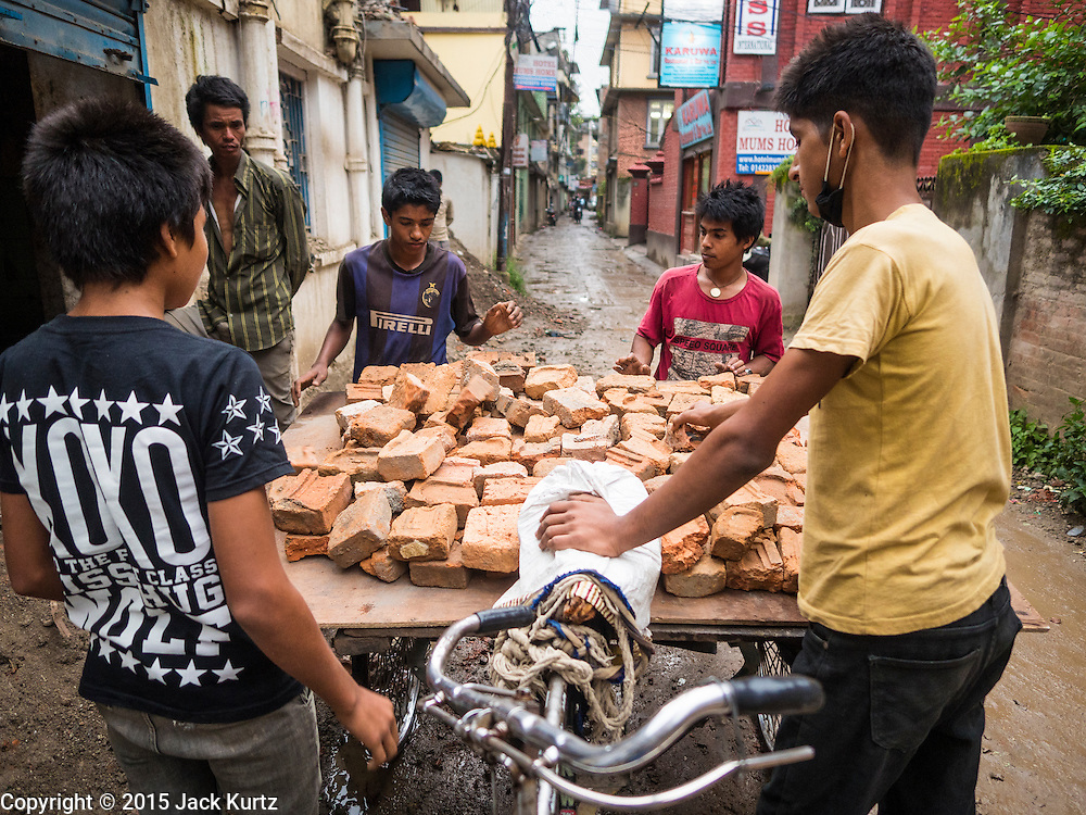 06 AUGUST 2015 - KATHMANDU, NEPAL: Laborers recycle bricks from a house in Kathmandu that was destroyed in the Nepal Earthquake. The Nepal Earthquake on April 25, 2015, (also known as the Gorkha earthquake) killed more than 9,000 people and injured more than 23,000. It had a magnitude of 7.8. The epicenter was east of the district of Lamjung, and its hypocenter was at a depth of approximately 15 km (9.3 mi). It was the worst natural disaster to strike Nepal since the 1934 Nepal–Bihar earthquake. The earthquake triggered an avalanche on Mount Everest, killing at least 19. The earthquake also set off an avalanche in the Langtang valley, where 250 people were reported missing. Hundreds of thousands of people were made homeless with entire villages flattened across many districts of the country. Centuries-old buildings were destroyed at UNESCO World Heritage sites in the Kathmandu Valley, including some at the Kathmandu Durbar Square, the Patan Durbar Squar, the Bhaktapur Durbar Square, the Changu Narayan Temple and the Swayambhunath Stupa. Geophysicists and other experts had warned for decades that Nepal was vulnerable to a deadly earthquake, particularly because of its geology, urbanization, and architecture.      PHOTO BY JACK KURTZ