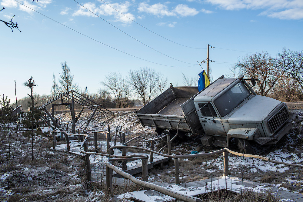 ARTEMIVSK, UKRAINE - FEBRUARY 19: A Ukrainian military truck lies in a ditch at the side of the road leading out of Debaltseve on February 19, 2015 in Artemivsk, Ukraine. Ukrainian forces started withdrawing from the strategic and hard-fought town of Debaltseve yesterday being effectively surrounded by pro-Russian rebels. (Photo by Brendan Hoffman/Getty Images) *** Local Caption ***
