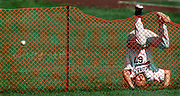 A Hispanic league outfielder goes over the webbed fencing an onto his head while chasing a long fly ball during game play.