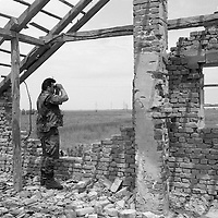 A Croatian soldier in Ivanovac peers across a open space where Serbian snipers were known to lay concealed.