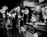 """Young female touts sent out on """"Walking Street"""" to attract male customers into a go-go bar.  Walking Street, which is lined with go-go bars and clubs, becomes a pedestrian street filled with a throng of tourists; male, female and even children every night.  Pattaya, Thailand."""
