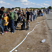 Refugees and migrants, mostly from Syria and Afghanistan being held in a field by Hungarian authorities, queuing up for food and other supplies provided by volunteer groups, close to the town of Röszke, just inside the Hungarian border from Serbia. The official border reception centres are full and refugees must camp on the ground.