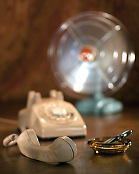 A vintage telephone rests on a table with the handset off the hook in the foreground.  An amber ashtray with a cigarette lighter is near the phone.  A vintage blue fan whirs in the background.