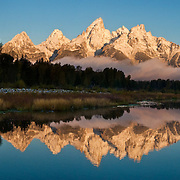 """Fresh snow dusts mountain peaks which reflect in the Snake River at Schwabacher Landing at sunrise in Grand Teton National Park, Wyoming, USA. Five images were stitched to make this panorama. Published in """"Light Travel: Photography on the Go"""" book by Tom Dempsey 2009, 2010."""