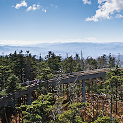 """A spiral ramp leads to a popular observation tower on Clingman's Dome, with a panoramic view of Great Smoky Mountains National Park of Tennessee and North Carolina, in southeastern USA. Clingmans Dome (6,643 feet or 2,025 meters elevation) is the highest mountain in the Great Smokies, the highest in Tennessee, the highest along the 2,174-mile (3,499 km) Appalachian Trail, and the third-highest mountain in the Appalachian range. A paved road connects it to U.S. Highway 441 (Newfound Gap Road). The summit is coated by a Spruce-fir (or """"boreal"""") forest, common in northern latitudes, but found only in the highest elevations in the southeastern United States. Clingmans Dome, like most of the Great Smokies, consists of a type of lightly metamorphosed sedimentary rock (especially sandstone) that is part of the Ocoee Supergroup formation, created from ancient ocean sediments nearly one billion years ago. The Smoky Mountains are among the oldest in the world, lifted approximately 200-300 million years ago in the Alleghenian orogeny. Panorama stitched from 6 overlapping photos."""