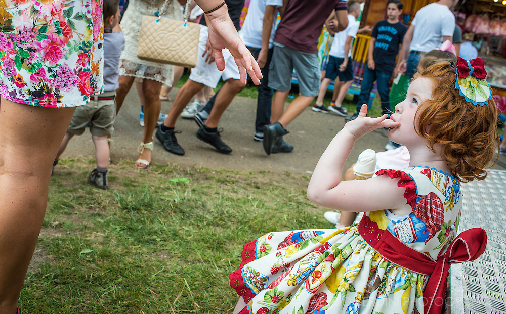 A ginger girl in her party dress licks her ice-creamy fingers. Being originally from Ireland, the travellers' comunity has a high percentage of ginger-haired people.