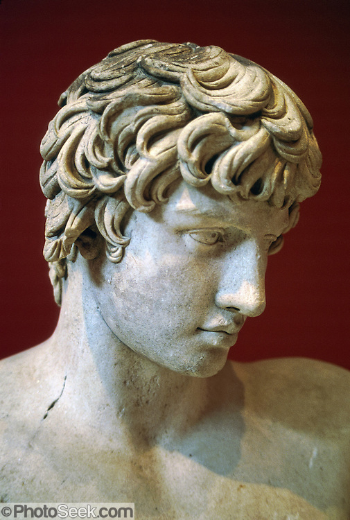 "In the National Archaeological Museum in Athens, Greece, see a sculpture of Antinoos (or Antinous), who lived about 110-130 AD and was Roman emperor Hadrian's lover and best friend. Hadrian lived 76-138 AD and become one of the few exemplary Roman sovereigns. Hadrian fell in love with the boy Antinous, who accompanied him on his extended trips through the Empire. At age 20, Antinous was drowned, or drowned himself, in the Nile. Cassius Dion recounts that Antinous had learned from an astrologer that he might in this way add his life-span to that of Hadrian's. The sovereign mourned for his friend for the rest of his life. He ordered the foundation of a city, Antinoopolis, at the place where Antinous had died. He surrounded himself with statues and busts of Antinous on his trips, and even more so at his old-age residence, the ""Villa"" in Tivoli. A star or constellation was named after Antinous."