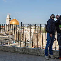 Israel, Jerusalem, Tourists take selfie snapshots of themselves at fence overlooking Western Wall and Temple Mount