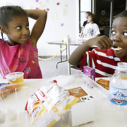 As part of the summer free lunch program, Ty'najion Hayes, 7, left, and her brother Tyrance Hayes, 5, eat their meal consisting of a sub sandwich, chips, fruit, vegetables and juice inside the former Big Bear store on Roberts Road on July 23. The lunch program feeds approximately 60 people a day and relies on volunteers from local churches, including the Upper Arlington Lutheran Church, to prepare the meals and feed the kids.