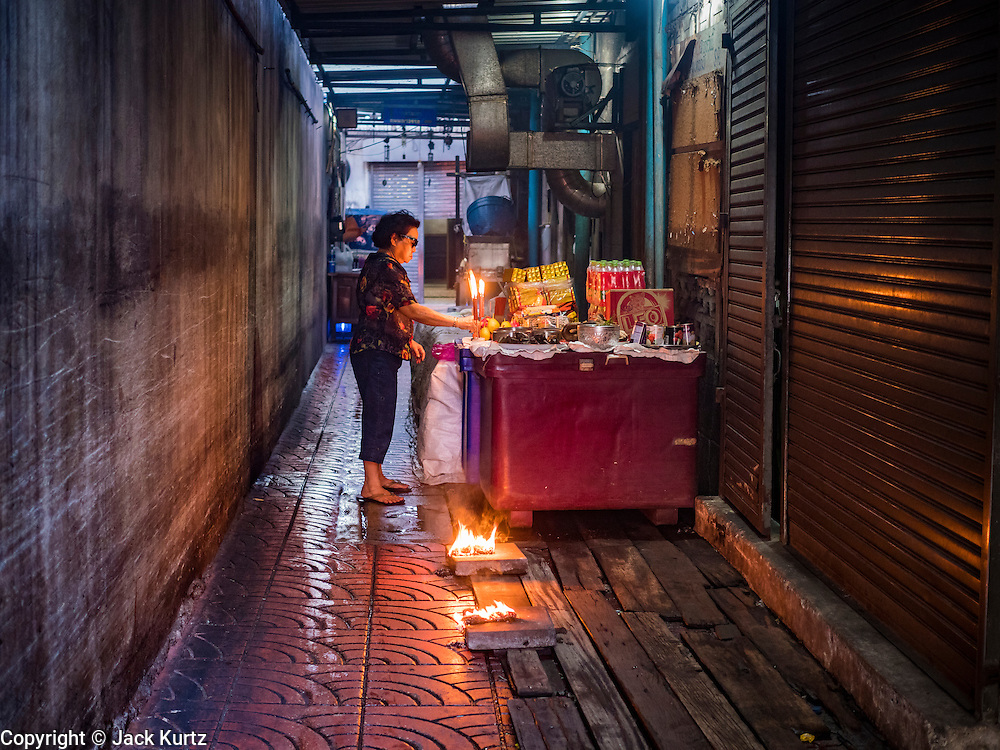 27 JANUARY 2017 - BANGKOK, THAILAND: A woman prays at homemade family altar in a soi (alley) in Bangkok's Chinatown on Chinese New Year in Bangkok. 2017 is the Year of the Rooster in the Chinese zodiac. This year's Lunar New Year festivities in Bangkok were toned down because many people are still mourning the death Bhumibol Adulyadej, the Late King of Thailand, who died on Oct 13, 2016. Chinese New Year is widely celebrated in Thailand, because ethnic Chinese are about 15% of the Thai population.       PHOTO BY JACK KURTZ