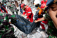 Padang, Western Sumatra, Indonesia, 7th October 2009:?Rescue workers work to remove the body of Lion Air stewardess Axel Alia  from the Ambacang Hotel in Padang which collapsed following a devastating earthquake in Western Sumatra that claimed the lives of an estimated 2000 people.?Photo: Joseph Feil