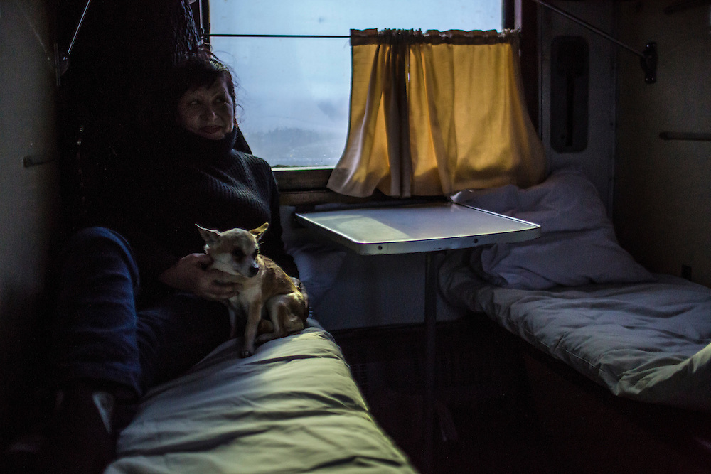 SLOVYANSK, UKRAINE - FEBRUARY 7, 2015: Natasha Kurta and her dog Gera, who were displaced by fighting in the town of Debaltseve, relax in the train in which they are temporarily being housed in Slovyansk, Ukraine. Many civilians have been evacuated from Debaltseve and brought to Slovyansk, where they are either given a free onward ticket or housed in the train or another facility until they can make further plans. CREDIT: Brendan Hoffman for The New York Times