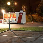 Bright lights illuminate a French ADA car rental kiosk in an empty car park alongside the N186 motorway in southern Paris.