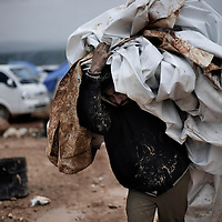 SYRIA, ATMEH. A man carries a muddy tent inside the camp for displaced Syrians in Atmeh on January 12, 2013. The camp is on the border with Turkey and is providing shelter to nearly 13,000 people; most of them are children. ALESSIO ROMENZI