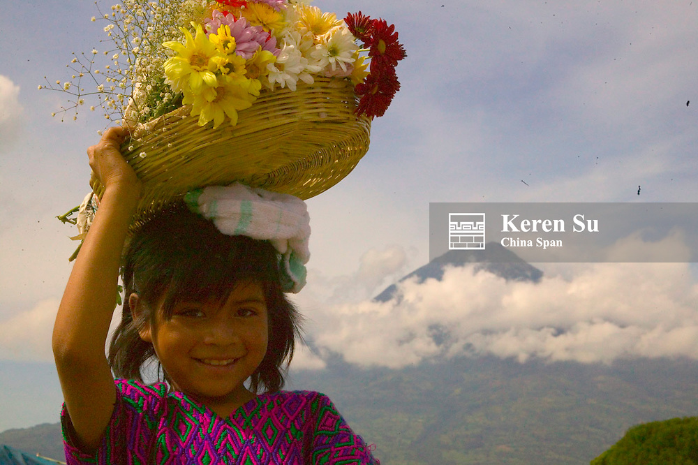 Girl carrying flower basket, Volcano Pacaya wrapped with clouds in the distance, Antigua, Guatemala